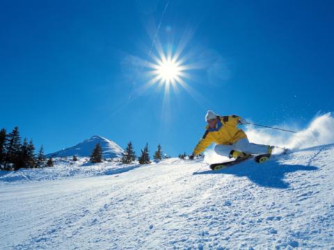 Skifahrer beim Skifahren in den Alpen bei blauem Himmel und Sonnenschein. JUFA Hotels bietet erholsamen Familienurlaub und einen unvergesslichen Winterurlaub.
