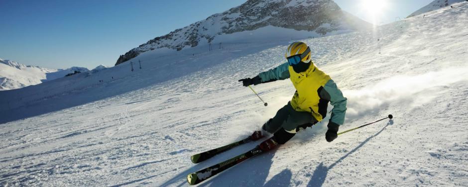 Skifahrer beim Skifahren bei Sonnenschein in den Alpen. JUFA Hotels bietet erholsamen Familienurlaub und einen unvergesslichen Winterurlaub.