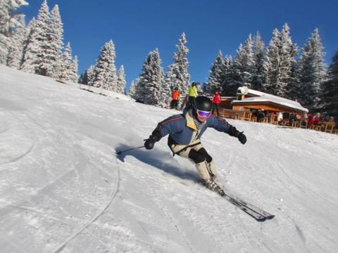 Frau fährt mit den Skier die perfekt präparierte Skipiste im Skigebiet Salzstiegl in der Steiermark hinunter. JUFA Hotels bietet erholsamen Familienurlaub und einen unvergesslichen Winterurlaub.