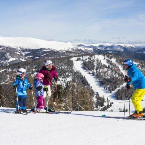 Familie beim Skifahren im wunderschönen Skigebiet Hochrindl in Kärnten. JUFA Hotels bietet erholsamen Familienurlaub und einen unvergesslichen Winterurlaub.