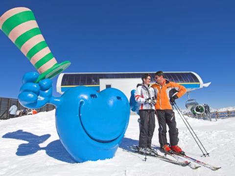 Ein Paar genießt einen wunderschönen Skitag im Skigebiet Katschberg und posiert gemeinsam beim Katschisphotopoint. JUFA Hotels bietet erholsamen Familienurlaub und einen unvergesslichen Winterurlaub.