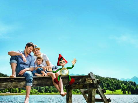Familie mit jungem Sohn am See sitzend mit Sparefroh-Maskottchen - 139241112