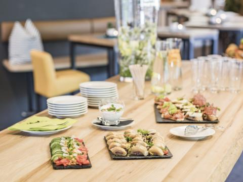 Ein Tisch mit kleinen Häppchen und Getränken während einer Kaffepause einer Veranstaltung. JUFA Hotels bietet den Ort für erfolgreiche und kreative Seminare in abwechslungsreichen Regionen.