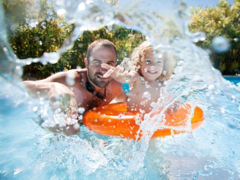Sie sehen einen Vater und seine Tochter spielend und planschend mit Schwimmreifen in einem Freibad. JUFA Hotels bietet erholsamen Thermen- und Badespass für die ganze Familie.