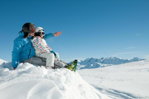 Ein Vater sitzt mit seinem Kind auf einem Gipfel im Schnee und zeigt ihm die Berge. JUFA Hotels bietet erholsamen Familienurlaub und einen unvergesslichen Winterurlaub.