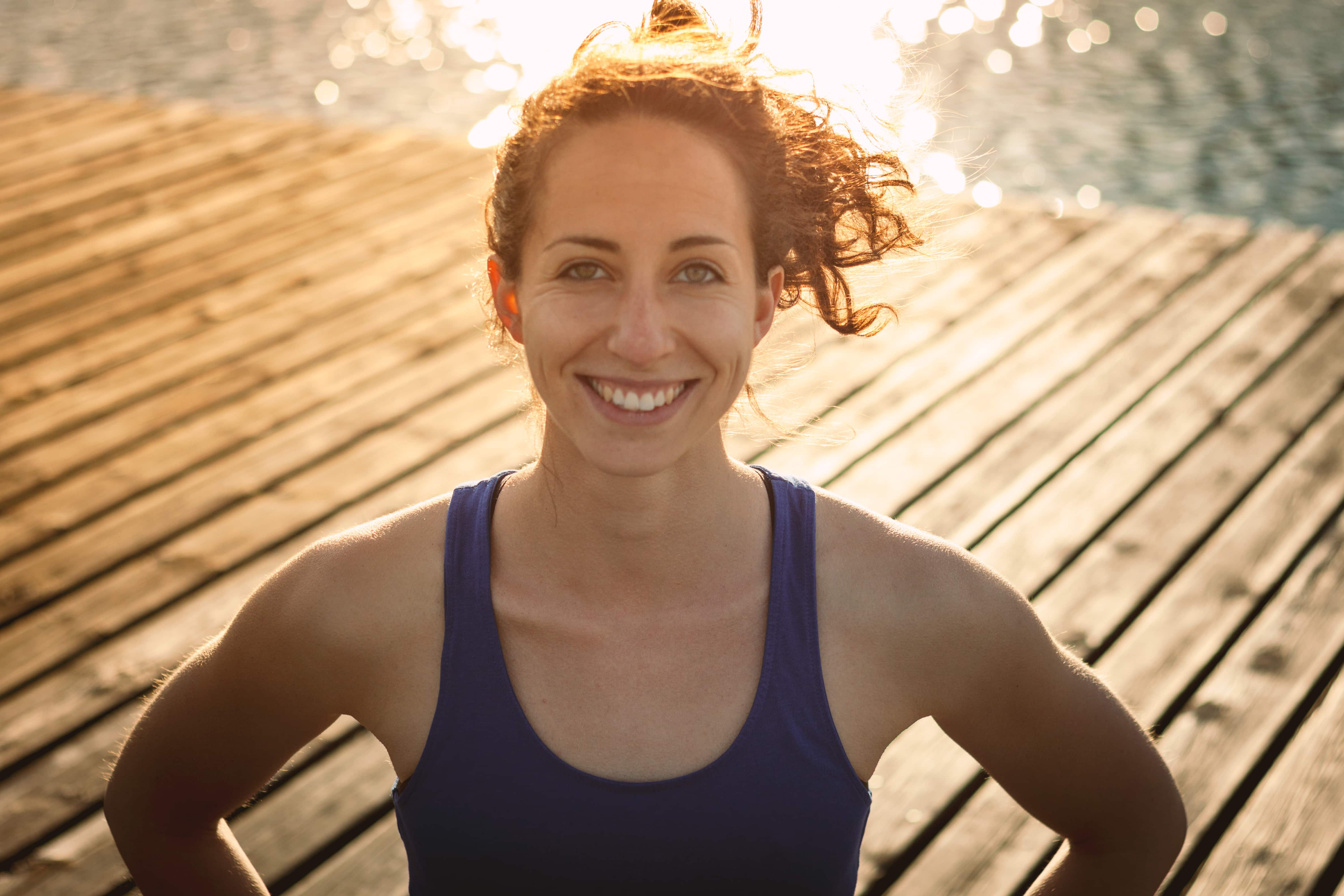 Ein Portraitfoto der JUFA Yoga Lehrerin Janina Brunner auf einem Steg am Wasser. JUFA Hotels bietet Ihnen den Ort für erfolgreiches Training in ungezwungener Atmosphäre für Vereine und Teams.