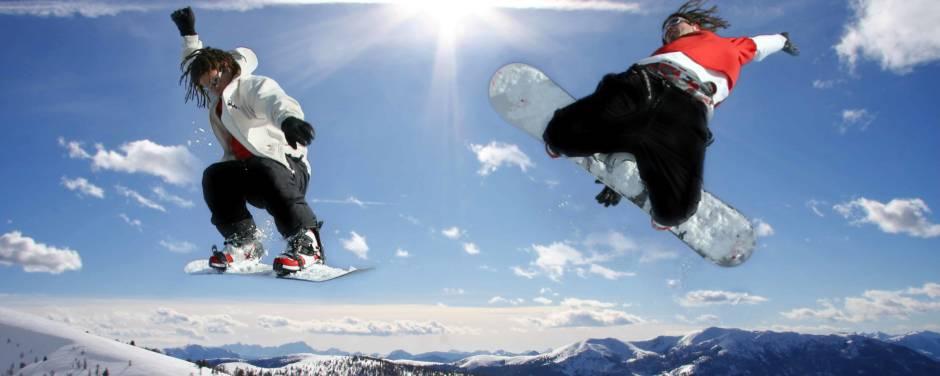 Zwei Snowboarder beim Snowboarden in den Alpen machen einen Sprung. JUFA Hotels bietet erholsamen Familienurlaub und einen unvergesslichen Winterurlaub.