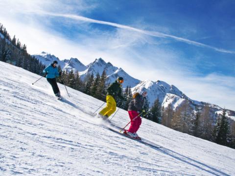 Eine Familie beim Skifahren im wunderschönen Familienskigebiet Maiskogel im Salzburger Land. JUFA Hotels bietet erholsamen Familienurlaub und einen unvergesslichen Winterurlaub.