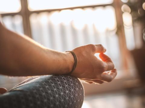Frauenhand bei eine Yogapose im Schneidersitz. JUFA Hotels bietet erholsamen Thermen- und Badespass für die ganze Familie.