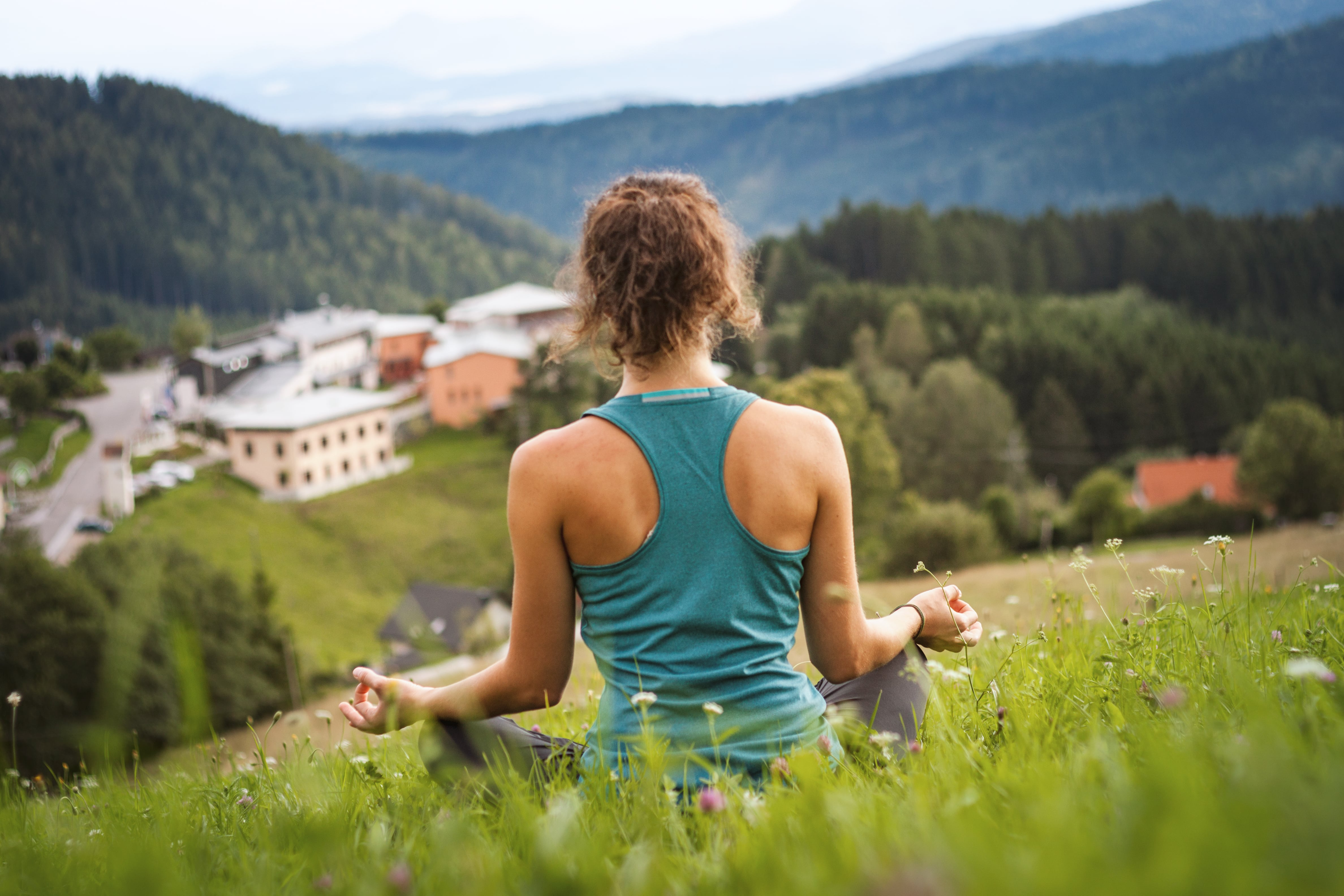 Eine junge Frau sitzt im Schneidersitz in einer Wiese und macht Yogaübungen. JUFA Hotels bietet erholsamen Thermen- und Badespass für die ganze Familie.