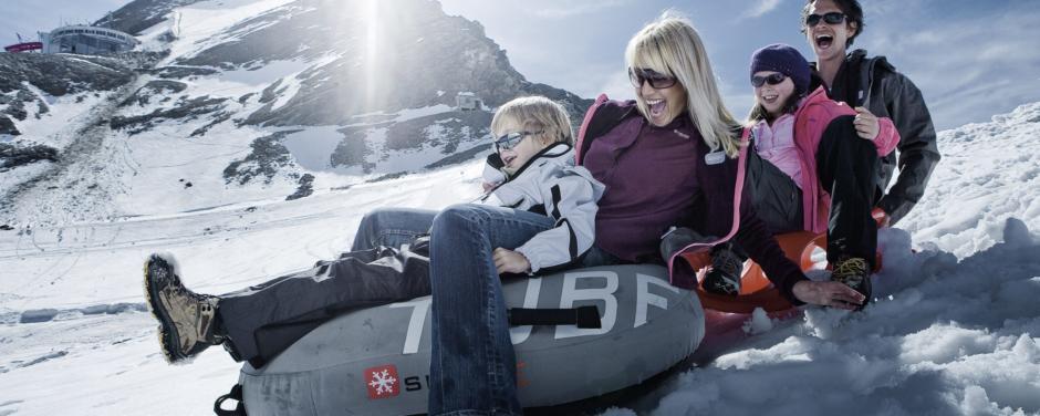 Familie hat Spaß auf der Rutschbahn der Ice Arena bei der Gipfelwelt 3000 auf dem Kitzsteinhorn. JUFA Hotels bieten erholsamen Familienurlaub und einen unvergesslichen Winter- und Wanderurlaub.