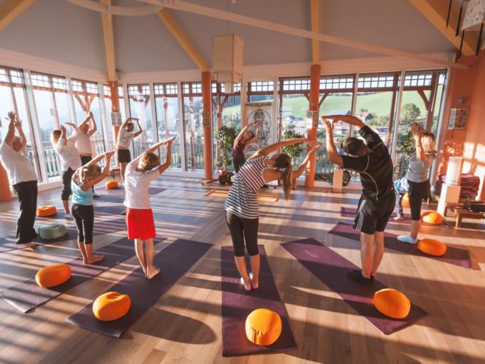 Eine gemischte Gruppe macht Yogaübungen im Sonnengrußraum im JUFA Hotel Knappenberg. JUFA Hotels bietet erholsamen Thermen- und Badespass für die ganze Familie.