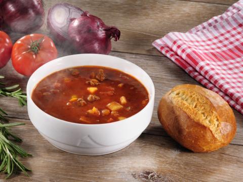 Eine Schüssel mit Gulaschsuppe mit einem Brötchen auf einem Tisch mit Rosmarin; Ziebeln und Tomaten. JUFA Hotels bieten regionlae, saisonale Küche mit Zutaten aus natürlichem Anbau.