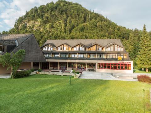 Außenansicht vom JUFA Hotel Almtal mit Garten im Sommer. JUFA Hotels bieten erholsamen Familienurlaub und einen unvergesslichen Winter- und Wanderurlaub.