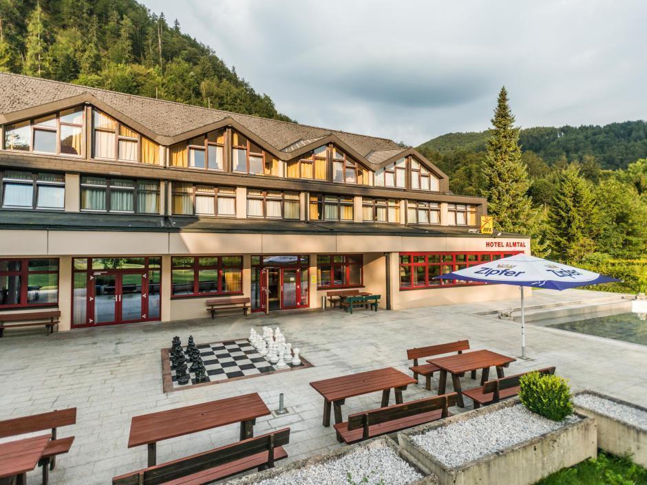 Außenansicht vom JUFA Hotel Almtal mit Sitzbänken auf der Terrasse im Sommer. JUFA Hotels bieten erholsamen Familienurlaub und einen unvergesslichen Winter- und Wanderurlaub.