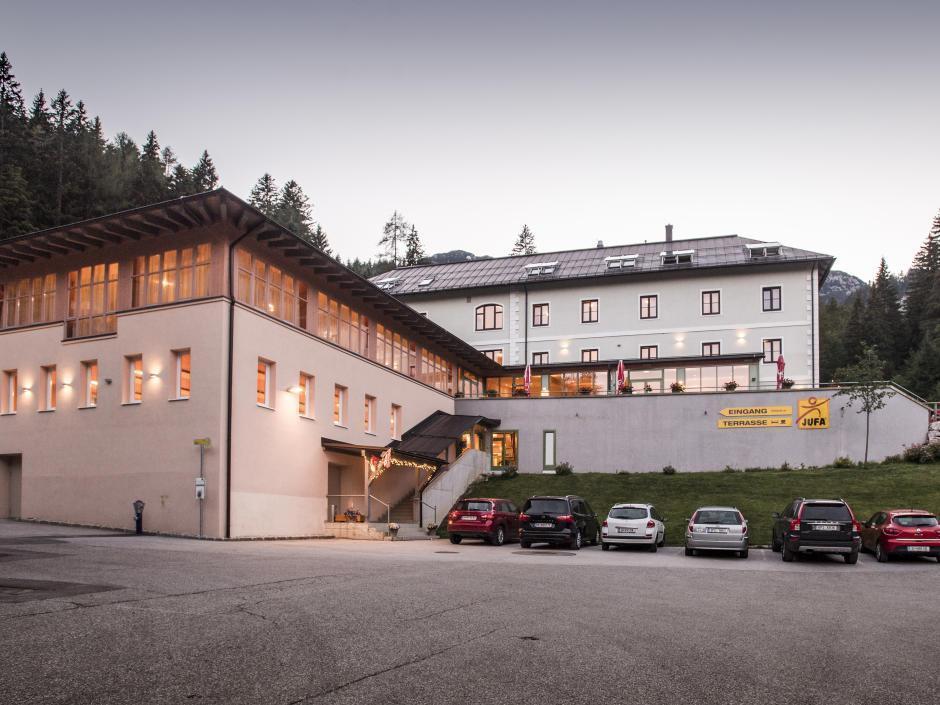 Außenansicht vom JUFA Hotel Altaussee mit Parkplatz bei Abendstimmung. JUFA Hotels bieten erholsamen Familienurlaub und einen unvergesslichen Winter- und Wanderurlaub.