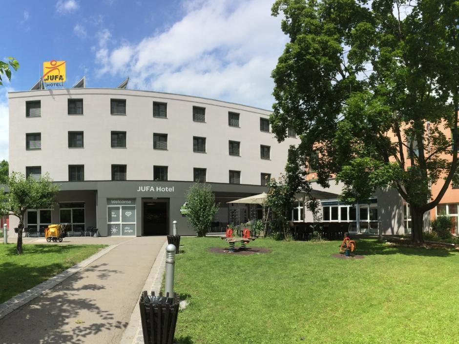 Aussenansicht mit Eigangsbereich und Garten vom JUFA Hotel Graz City. Der Ort für erlebnisreichen Städtetrip für die ganze Familie und der ideale Platz für Ihr Seminar.
