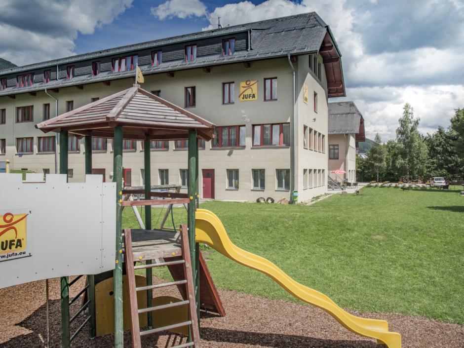 Außenansicht vom JUFA Hotel Lungau mit Kletterburg im Vordergrund. JUFA Hotels bieten erholsamen Familienurlaub und einen unvergesslichen Winter- und Wanderurlaub.