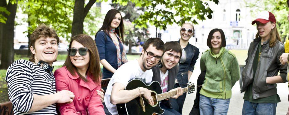 Eine Gruppe Jugendlicher sitzen im Park und einer spielt auf der Gitarre. JUFA Hotels bietet erlebnisreiche und kreative Schulprojektwochen in abwechslungsreichen Regionen.