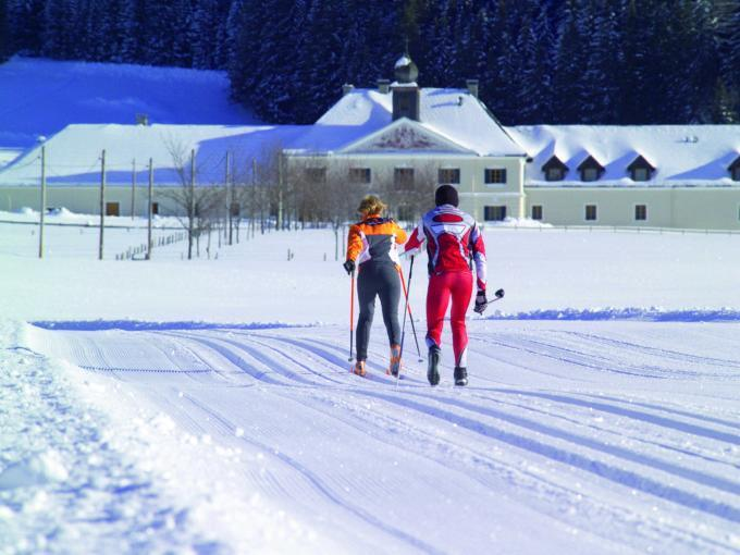 Sie sehen Langläufer auf der Loipe im Winter in Kaiserau bei Admont mit Gebäuse im Hintergrund. JUFA Hotels bietet erholsamen Familienurlaub und einen unvergesslichen Winterurlaub.