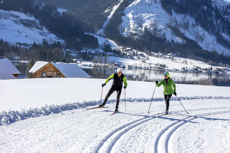 Paar beim Langlaufen und Skating am Grundlsee im wunderschönen Ausseerland. JUFA Hotels bietet erholsamen Familienurlaub und einen unvergesslichen Winterurlaub.