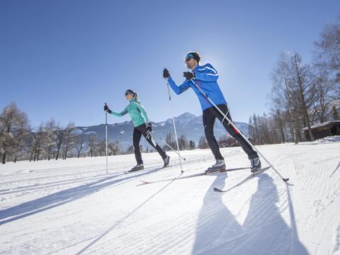 Ein Paar beim klassischen Langlaufen und Skating in Zell am See-Kaprun im Salzburger Land. JUFA Hotels bietet erholsamen Familienurlaub und einen unvergesslichen Winterurlaub.