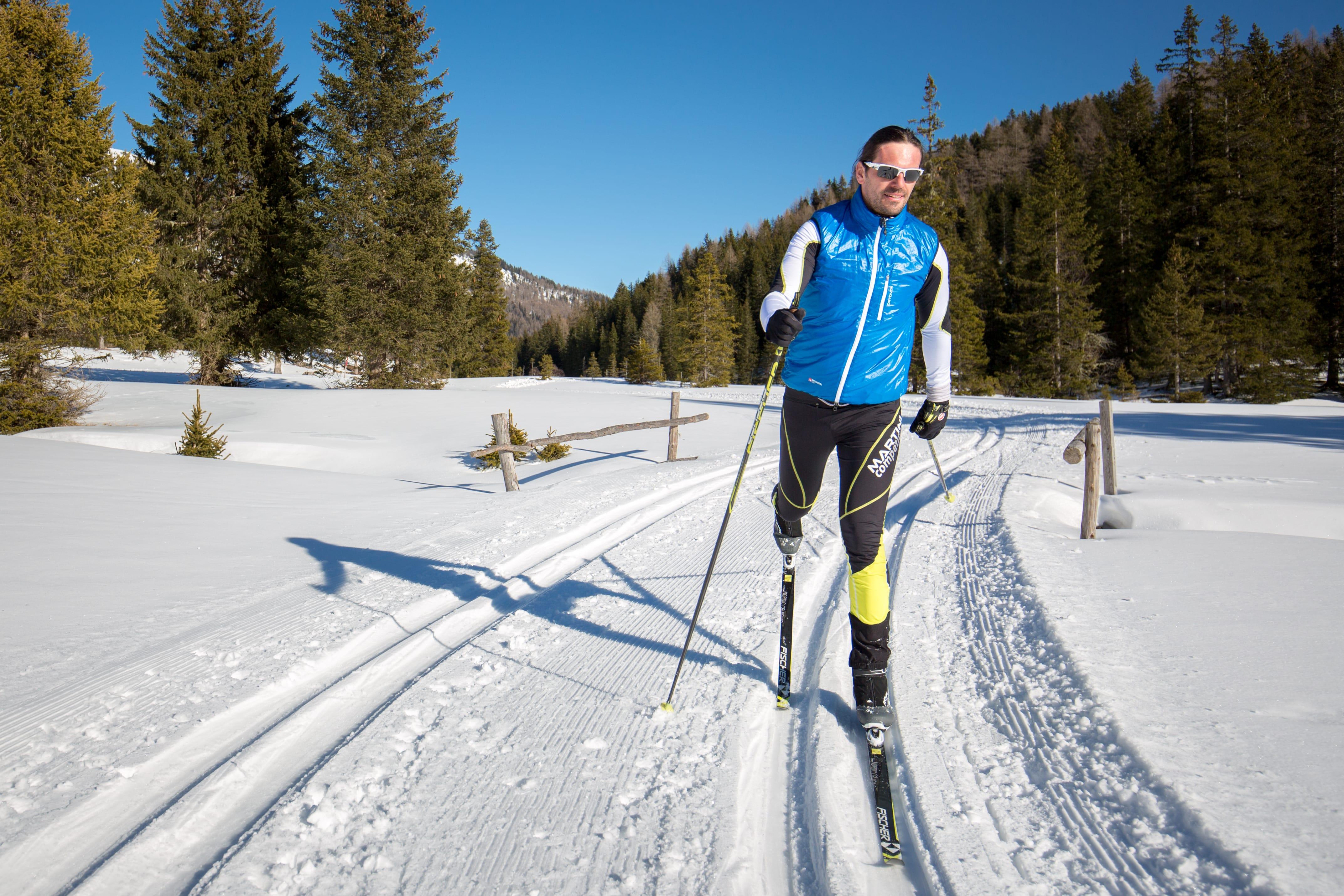 Mann beim klassischen Langlaufen auf perfekt präparierter Loipe durch die wunderschöne Landschaft der Ferienregion Lungau im Salzburger Land.