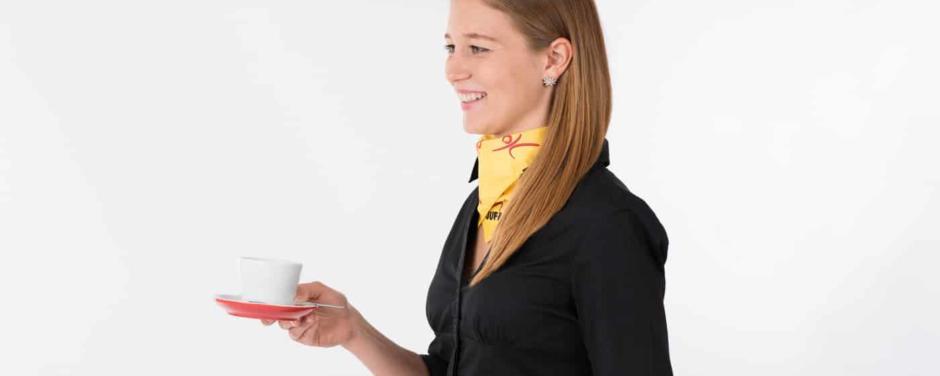 Eine Servicemitarbeiterin im JUFA-Outfit trägt eine Kaffeetasse. JUFA Hotels bietet Ihnen einen interessanten, abwechslungsreichen Arbeitsplatz in einem tollen Team in den schönsten Regionen in Österreich, Deutschland, Liechtenstein und Ungarn.