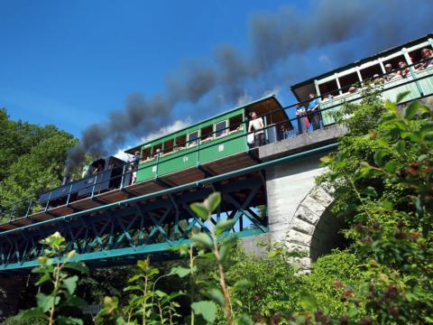 Eine Gruppe von Menschen sitzt in den Waggons im Ötscherland Express und tuckert über eine Brücke. JUFA Hotels bieten erholsamen Familienurlaub und einen unvergesslichen Winter- und Wanderurlaub.