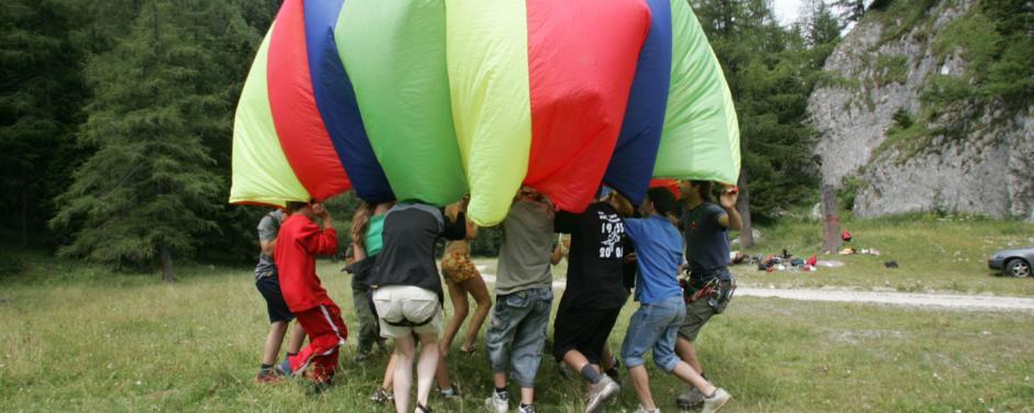 Kinder bilden über ihren Köpfen einen bunten Fallschirm. JUFA Hotels bietet erlebnisreiche Feriencamps in den Bereichen Sport, Gesundheit, Bildung und Sprachen.