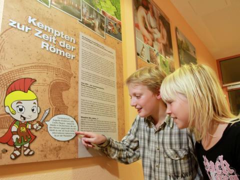 Zwei Kinder informieren sich über die Römerzeit in Kempten via Infotafeln im JUFA Kempten Familien-Resort. Der Ort für kinderfreundlichen und erlebnisreichen Urlaub für die ganze Familie.
