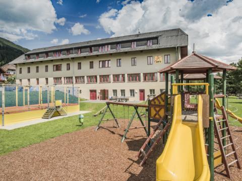 Kletterburg und Trampolin auf dem Spielplatz vom JUFA Hotel Lungau im Sommer. JUFA Hotels bieten erholsamen Familienurlaub und einen unvergesslichen Winter- und Wanderurlaub.