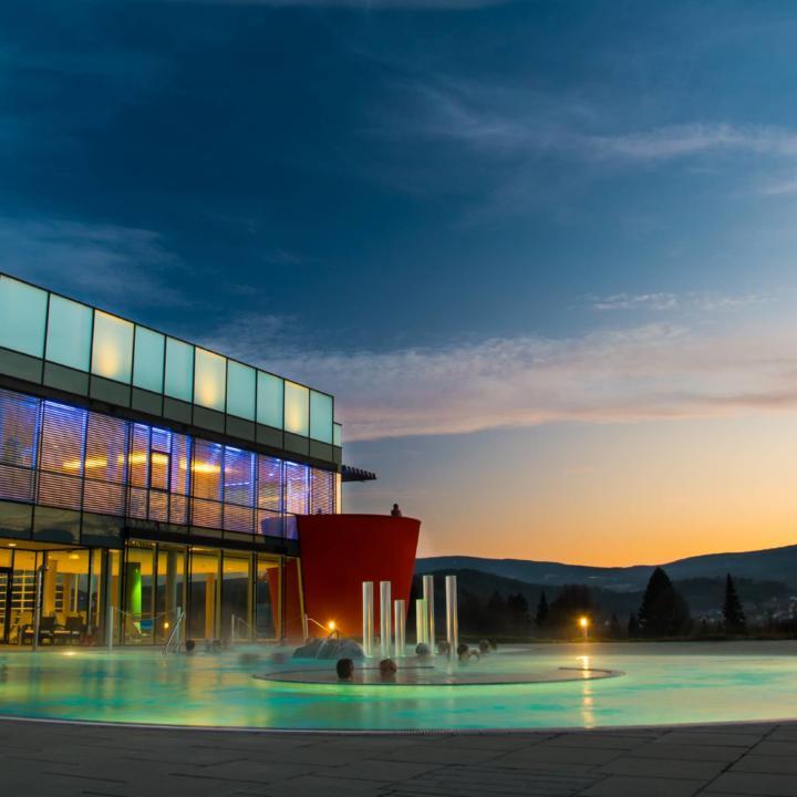Badegäste relaxen im Außenbecken der Therme Nova in Köflach bei Abendstimmung. JUFA Hotels bieten erholsamen Familienurlaub und einen unvergesslichen Winter- und Wanderurlaub.