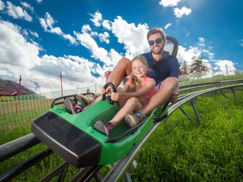 Vater und Tochter flitzen an einem Sommertag mit dem Maisiflitzer ins Tal. JUFA Hotels bietet kinderfreundlichen und erlebnisreichen Urlaub für die ganze Familie.
