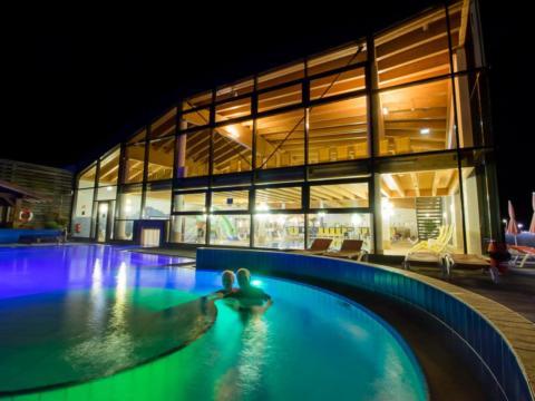 Ein älteres Paar relaxt im Außenbecken im Ybbstaler Solebad bei Nacht. JUFA Hotels bieten erholsamen Familienurlaub und einen unvergesslichen Winter- und Wanderurlaub.