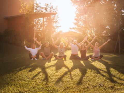 Eine Yogagruppe sitzt bei Sonnenuntergang auf einer Wiese und posiert für ein Gruppenbild in der Nähe von JUFA Hotels. Der Ort für erholsamen Familienurlaub und einen unvergesslichen Winter- und Wanderurlaub.