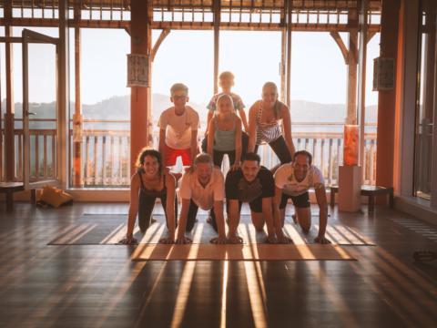 Eine Yogagruppe posiert für ein Gruppenfoto im Sonnengrußraum bei Sonnenuntergang JUFAA Hotels, der Ort für erholsamen Familienurlaub und einen unvergesslichen Winter- und Wanderurlaub.