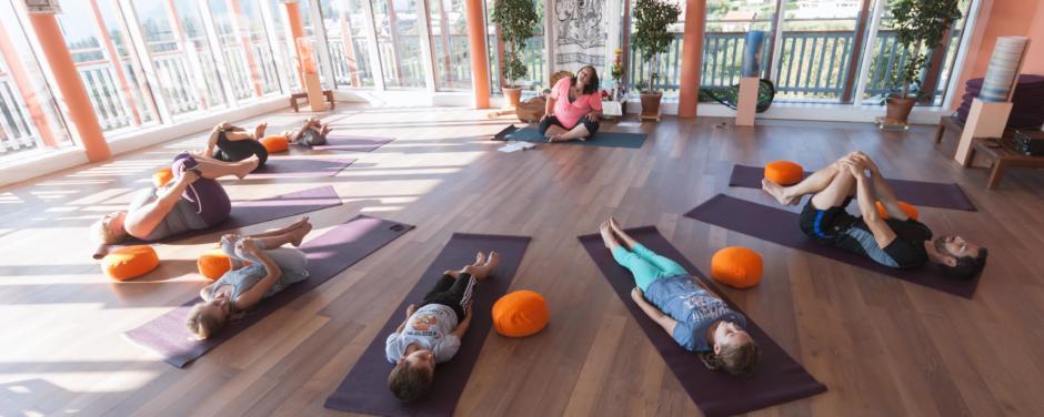 Eine Yogagruppe liegt auf Matten und macht Yogaübungen im Sonnengrußraum des JUFA Hotel Knappenberg. Der Ort für erholsamen Familienurlaub und einen unvergesslichen Winter- und Wanderurlaub.