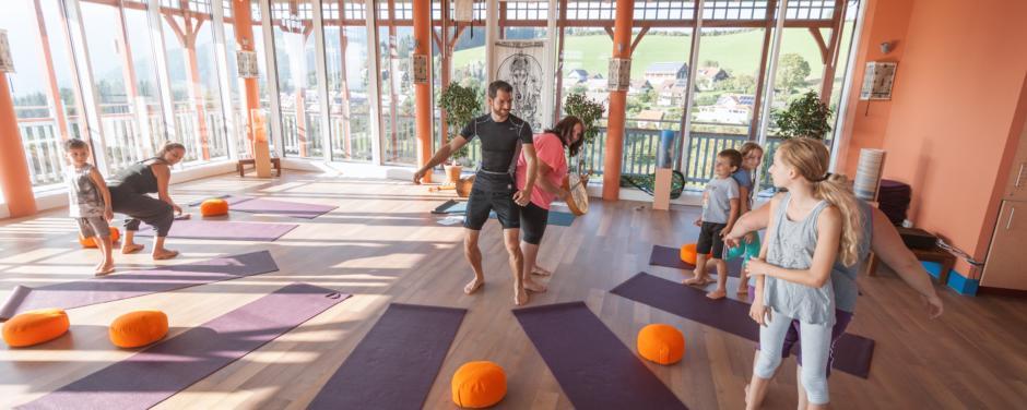 Eine Yogagruppe mit Yogamatten im Sonnengrußraum des JUFA Hotel Knappenberg. Der Ort für erholsamen Familienurlaub und einen unvergesslichen Winter- und Wanderurlaub.