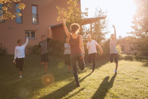 Eine Yogagruppe macht yogaübungen im Freien bei Sonnenuntergang in der Nähe vom JUFA Hotel Knappenberg. Der Ort für erholsamen Familienurlaub und einen unvergesslichen Winter- und Wanderurlaub.