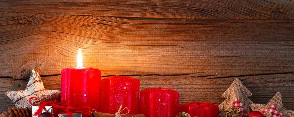Sie sehen einen Adventskranz mit roten Kerzen, Dekoration im Schnee. JUFA Hotels bietet erholsamen Familienurlaub und einen unvergesslichen Winterurlaub.