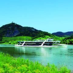 Ein Aussflugsschiff am Rhein vor Drachenfels im Sommer.JUFA Hotels bietet erlebnisreiche Städtetrips für die ganze Familie und den idealen Platz für Ihr Seminar.