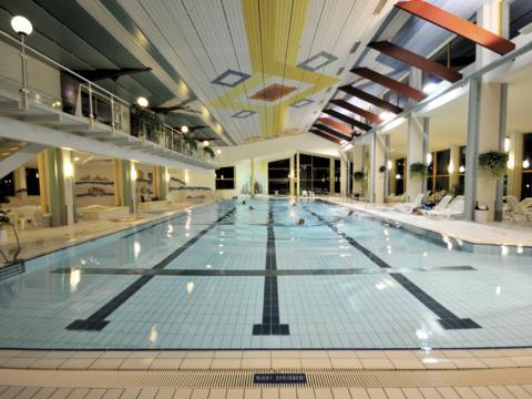 Badegästen beim Schwimmen im Innenbecken der Badeinsel Tamsweg. JUFA Hotels bieten erholsamen Familienurlaub und einen unvergesslichen Winter- und Wanderurlaub.