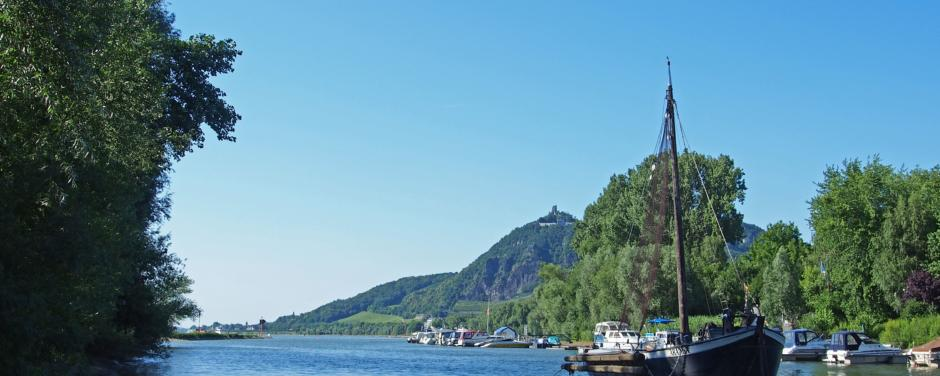 Boote am Rhein mit Drachenfels im Hintergrund im Sommer. JUFA Hotels bietet erlebnisreiche Städtetrips für die ganze Familie und den idealen Platz für Ihr Seminar.