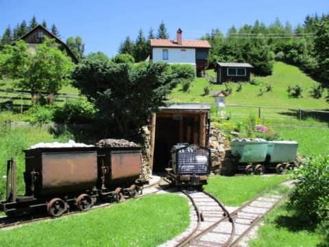 Grubenbahnmuseum Knappenberg mit Ausstellungsstücken auf einer Gleisanlage im Freien. JUFA Hotels bieten erholsamen Familienurlaub und einen unvergesslichen Winter- und Wanderurlaub.