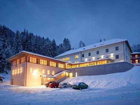 Außenansicht vom JUFA Hotel Altaussee mit Parkplatz bei Abendstimmung im Winter. JUFA Hotels bietet erholsamen Familienurlaub und einen unvergesslichen Winterurlaub.