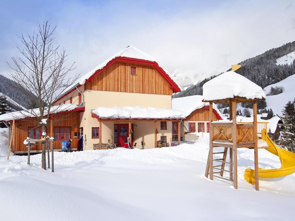 Aussenansicht im Winter mit verschneitem Spielplatz vom JUFA Hotel Donnersbachwald – Almerlebnis. Der Ort für erholsamen Familienurlaub und einen unvergesslichen Winter- und Wanderurlaub.