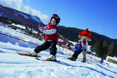 Kinder am Übungslift im Kinderskiland im Skigebiet Mariazeller Bürgeralpe. JUFA Hotels bietet erholsamen Familienurlaub und einen unvergesslichen Winterurlaub.