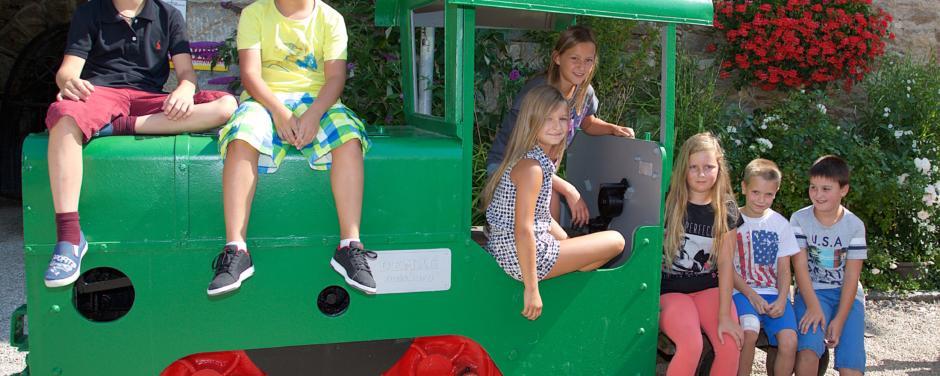 Kinder sitzen im Sommer auf einer grünen Lokomotive vorm Schaubergwerk in der Nähe vom JUFA Hotel Knappenberg. Der Ort für erlebnisreiche und kreative Schulprojektwochen in abwechslungsreichen Regionen.