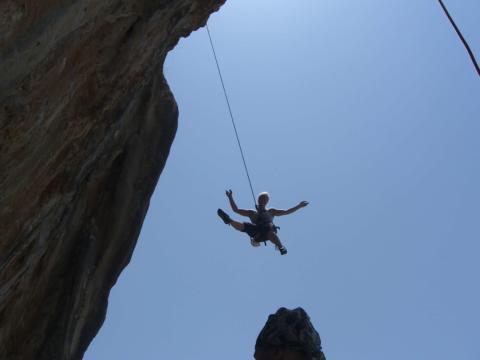 Ein Kletterer wird an einem Seil vor blauem Himmel abgeseilt. JUFA Hotes bietet erholsamen Familienurlaub und einen unvergesslichen Winter- und Wanderurlaub.